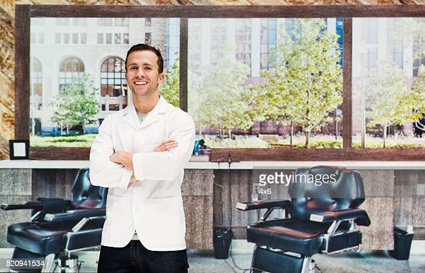 Cheerful barber standing in hair salon