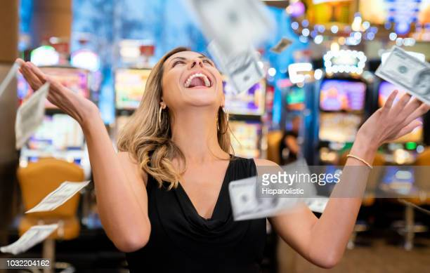 cheerful beautiful woman excited about all the money she won at the casino throwing to the air - casino stock pictures, royalty-free photos & images