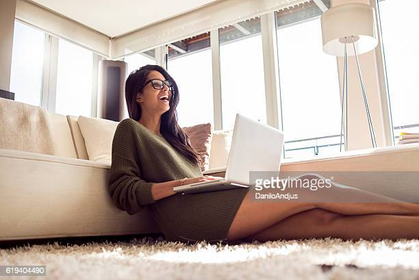 cheerful beautiful young woman using her laptop