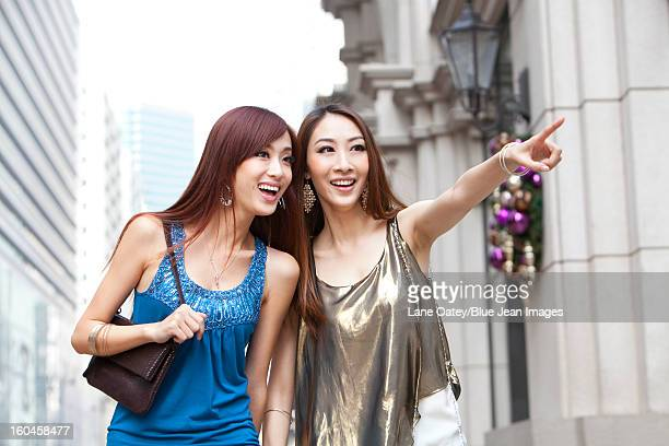 cheerful best female friends go shopping in hong kong - shoulder bag stock pictures, royalty-free photos & images