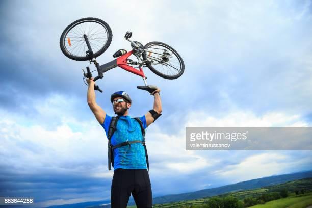 Cheerful biker lifting up his bike