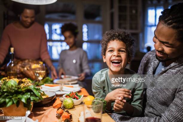 cheerful black boy with his father at dining table. - kids thanksgiving stock pictures, royalty-free photos & images