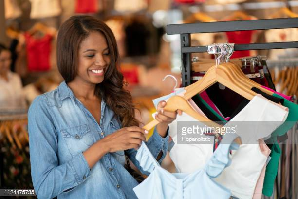 cheerful black customer holding a blouse from clothes rack smiling - hispanolistic stock photos and pictures