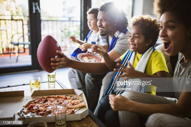 cheerful black family cheering while watching rugby match on tv at home. - match sportivo foto e immagini stock