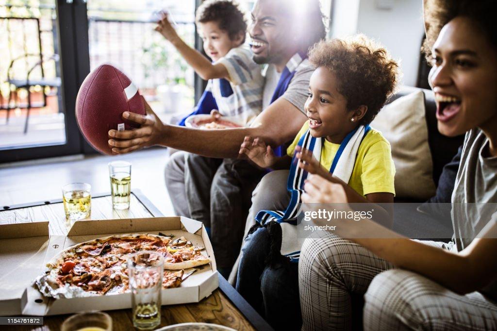 Joyeuse famille noire acclamant tout en regardant le match de rugby à la télévision à la maison. : Photo