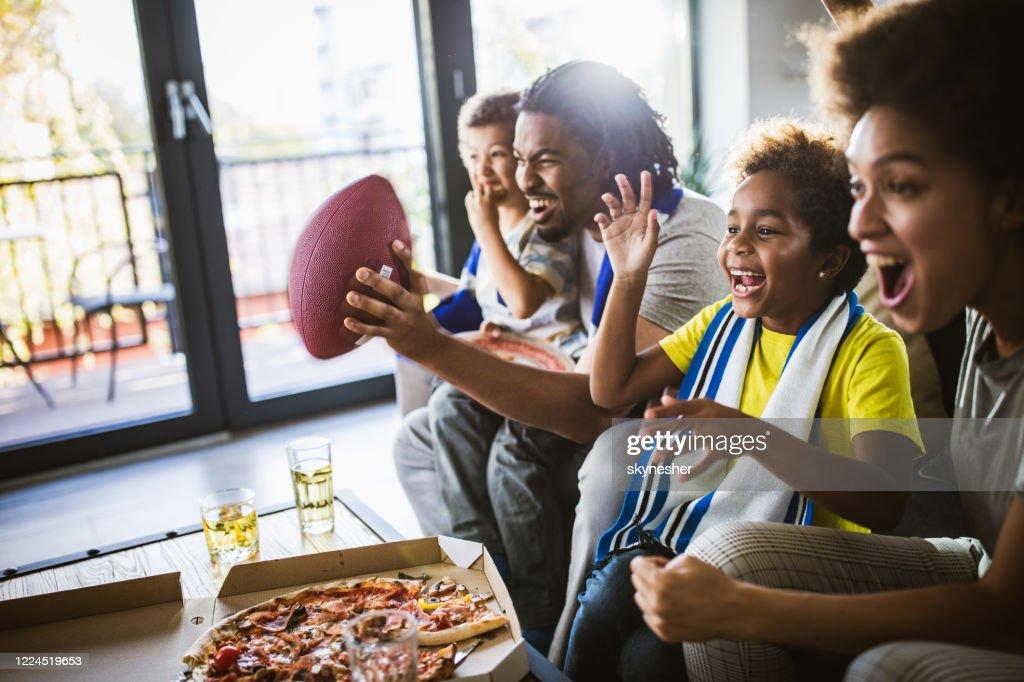 Het vrolijke zwarte familie toejuichen terwijl het letten van rugby op TV thuis. : Stockfoto