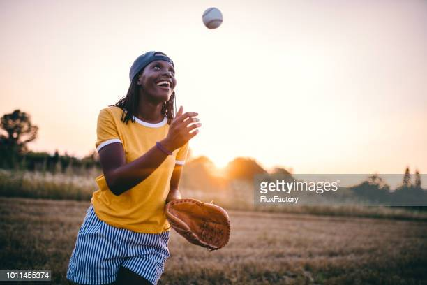 cheerful black girl playing baseball - throwing stock pictures, royalty-free photos & images