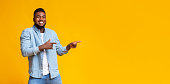 Cheerful black guy pointing two fingers aside at copy space