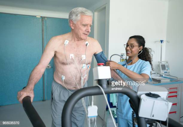 Cheerful black nurse checking the blood pressure on a senior patient doing a stress test on a treadmill