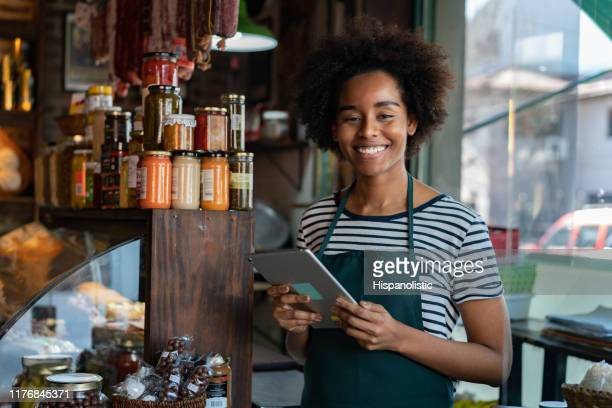 cheerful black saleswoman at a delicatessen holding a tablet while facing camera smiling - convenience store stock pictures, royalty-free photos & images