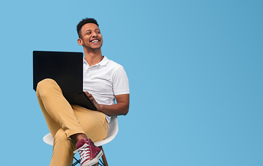 Cheerful black student with laptop looking away 1161071016
