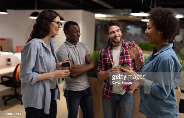 cheerful black woman discussing project with colleagues during break - coworker stock pictures, royalty-free photos & images