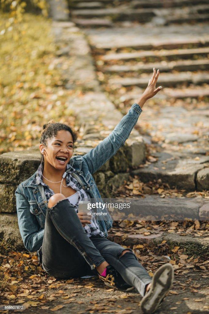 Stets gut gelaunte schwarze Frau in MP3-Musik im Park genießen. : Stock-Foto