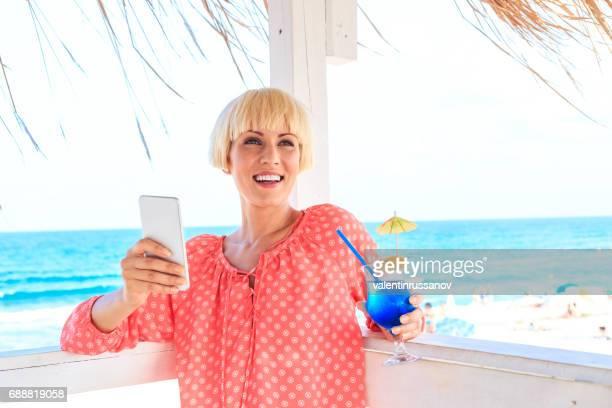 Fröhliche blonde Frau ausruhen und blauen Cocktail trinken