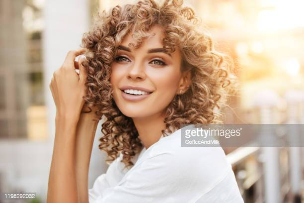 cheerful blond woman smiling and enjoying outdoor during a beautiful sunset - curly stock pictures, royalty-free photos & images