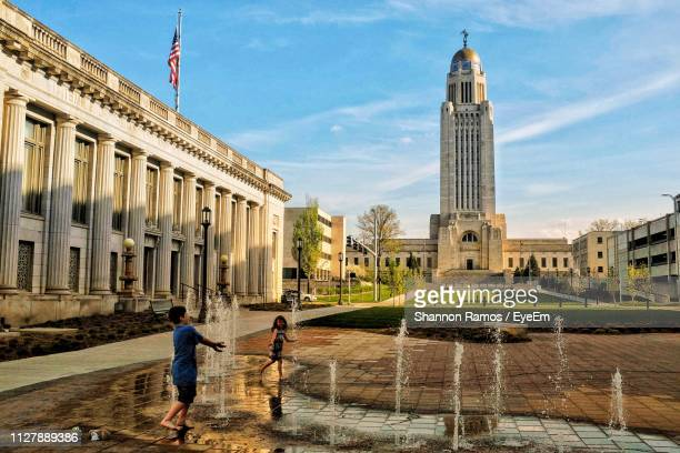 cheerful boy and girl standing at fountain in city against sky - nebraska stock photos and pictures