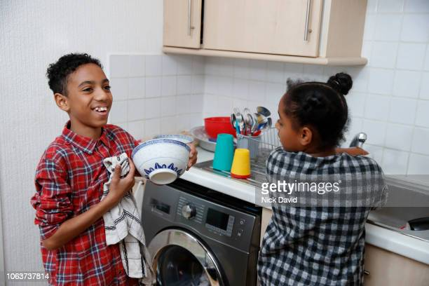 cheerful boy drying dishes with his sister - chores stock pictures, royalty-free photos & images
