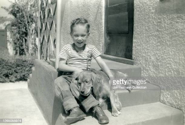 A cheerful boy in a striped tshirt sits on the steps of his parents' house as a dog lays down in his lap circa 1943