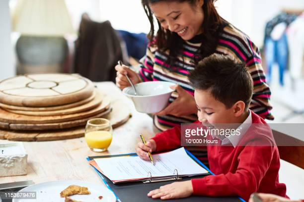 cheerful boy in school uniform doing homework with mother smiling - routine stock pictures, royalty-free photos & images