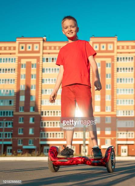 cheerful boy is riding on self-balance scooter - hoverboard stock pictures, royalty-free photos & images