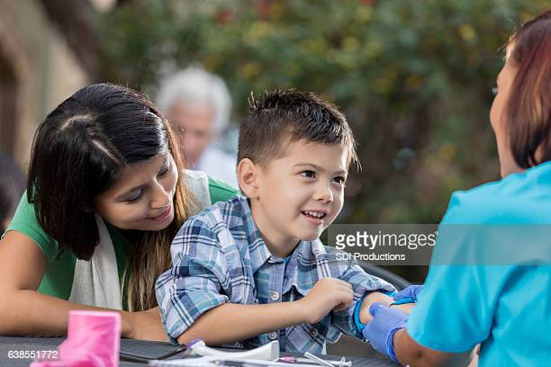 Cheerful boy receives medical exam at outdoor clinic