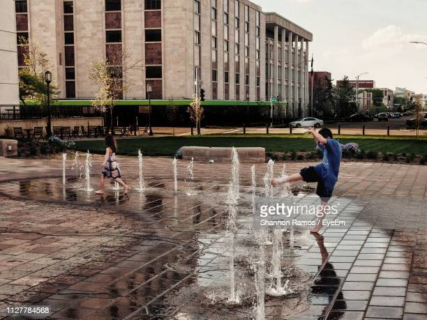 Cheerful Boy Standing At Fountain In City Against Sky