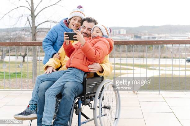 cheerful boy taking selfie with father and brother on wheelchair in park - persons with disabilities stock pictures, royalty-free photos & images