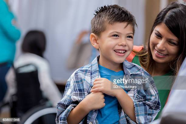Cheerful boy talks with doctor during well check