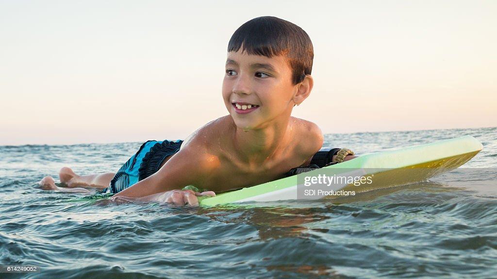 Cheerful boy uses body board in ocean : Stock Photo