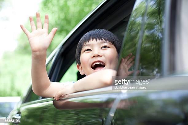 Cheerful boy waving out of car window