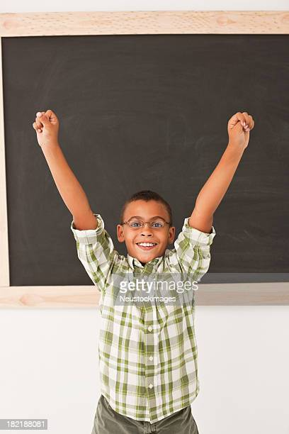 Cheerful boy with hands raised at classroom