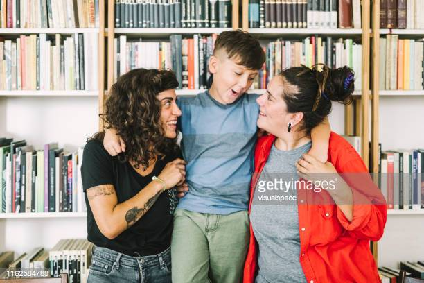 fröhlicher junge mit müttern zu hause - lesbische stock-fotos und bilder
