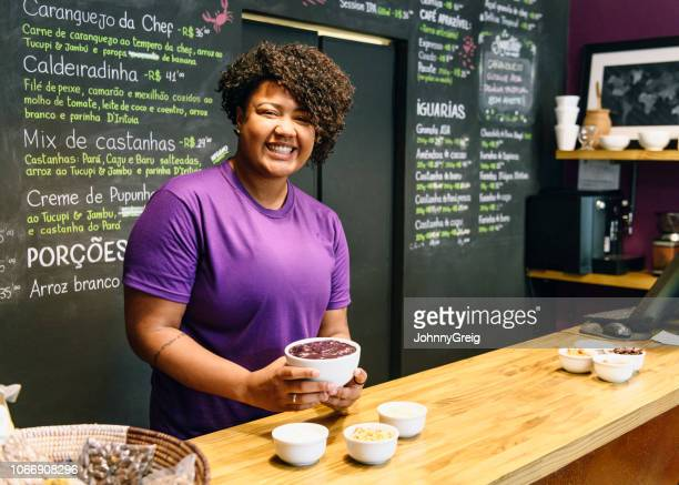 cheerful brazilian woman behind counter in açai cafe - entrepreneur stock pictures, royalty-free photos & images
