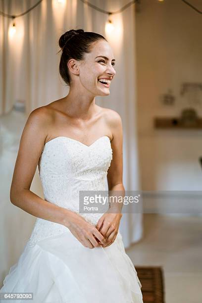 Cheerful bride in gown standing at bridal shop