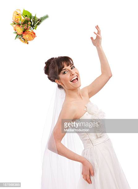 Cheerful bride throwing her bouquet of flowers