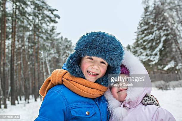 a cheerful brother and sister in warm winter clothing outdoors in winter - nur kinder stock-fotos und bilder