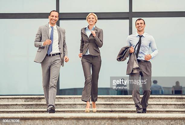 Cheerful business colleagues running down on stairs.