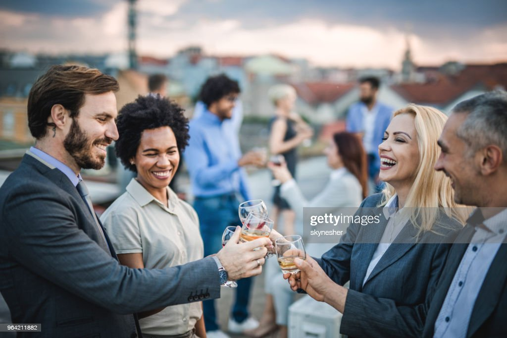 Cheerful business colleagues toasting with alcohol at the outdoor party. : Stock Photo