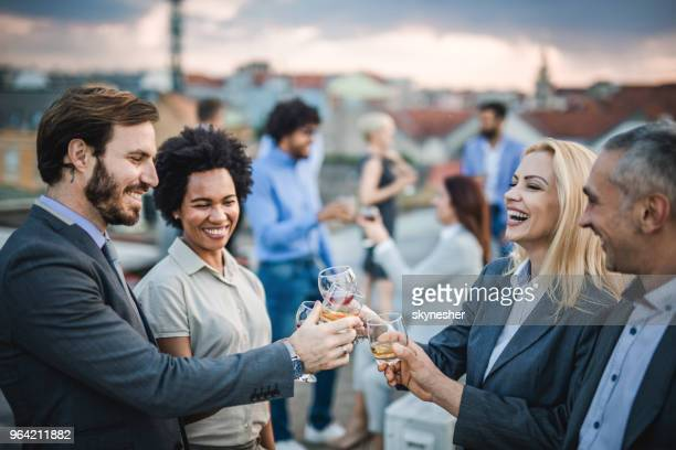 cheerful business colleagues toasting with alcohol at the outdoor party. - outdoor party stock pictures, royalty-free photos & images