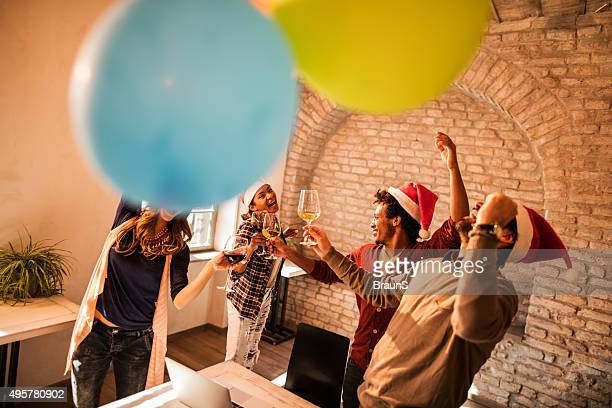 Cheerful business friends dancing on a Christmas office party.
