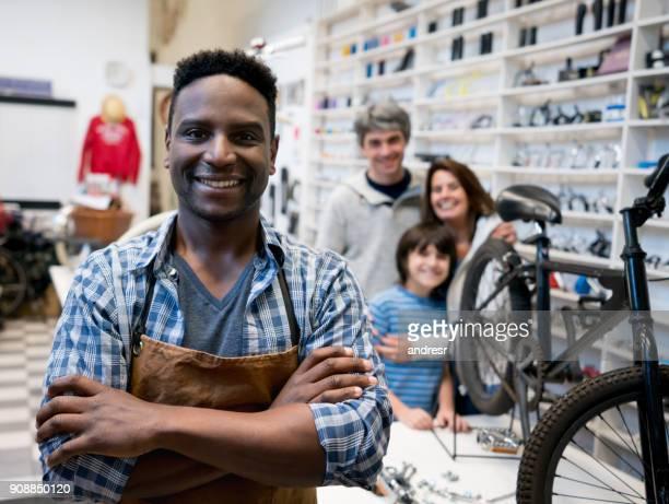 Propriétaire d'un magasin de vélo regardant sourire caméra gai