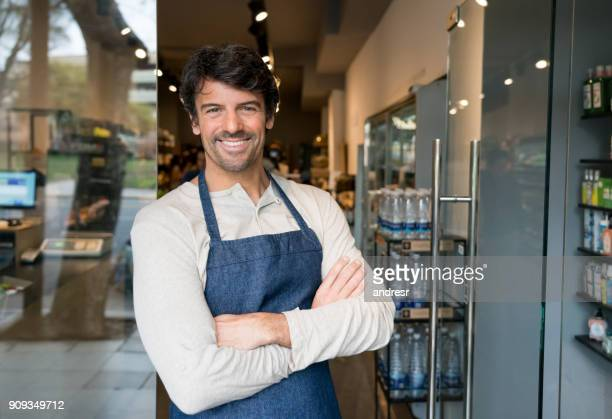 cheerful business owner of an organic market standing at the entrance smiling - salesman stock pictures, royalty-free photos & images
