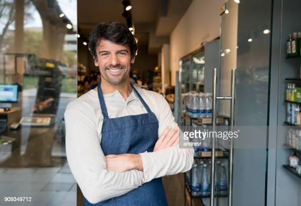 alegre, empresário de uma permanente do mercado orgânico no sorrindo a entrada - trabalho comercial - fotografias e filmes do acervo