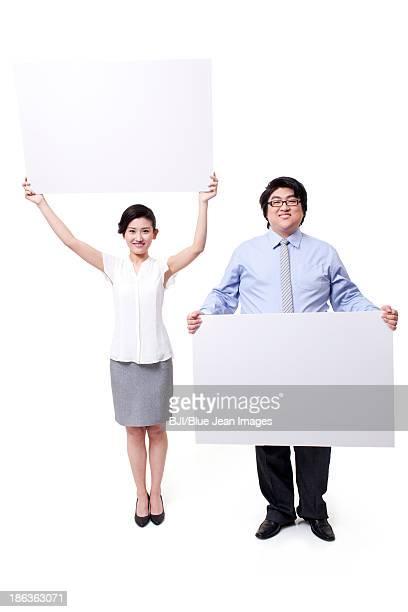 Cheerful business partner holding whiteboard aloft