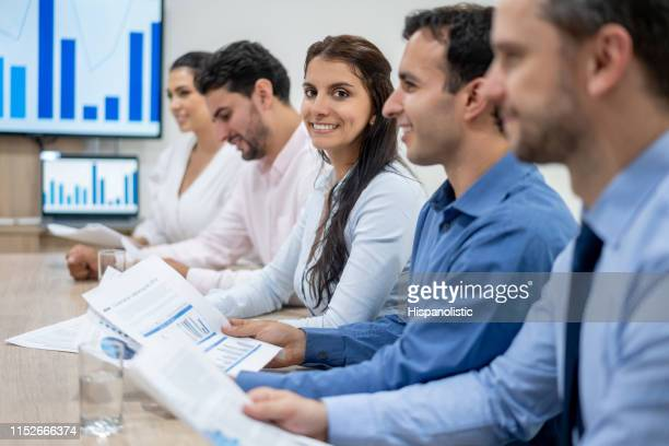 cheerful business people in a meeting and woman facing camera smiling - hispanolistic stock photos and pictures