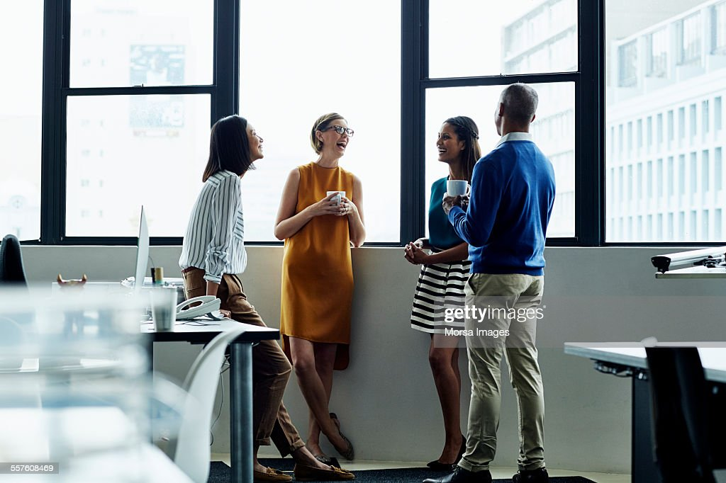 Cheerful business people standing by office window : Stock Photo