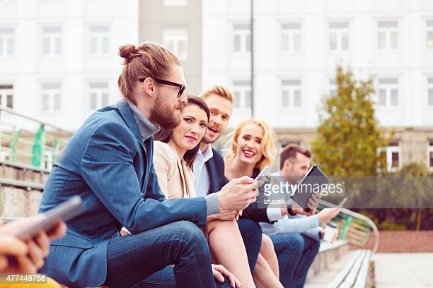 cheerful business team talking outdoor - izusek stock photos and pictures