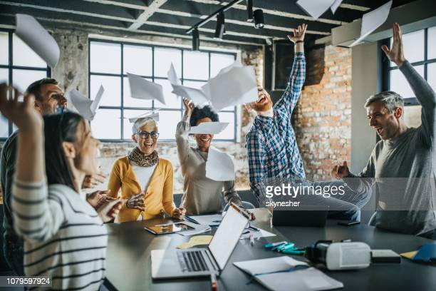 cheerful business team throwing papers up in the air at office. - lanciare foto e immagini stock