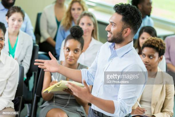 Cheerful businessman address a group of businesspeople during seminar