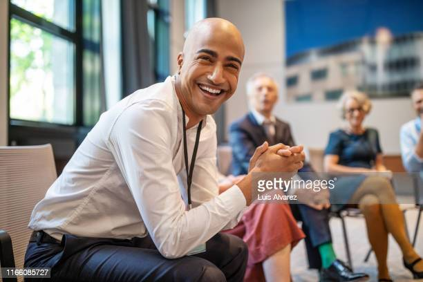 cheerful businessman at networking seminar - panel discussion stock pictures, royalty-free photos & images